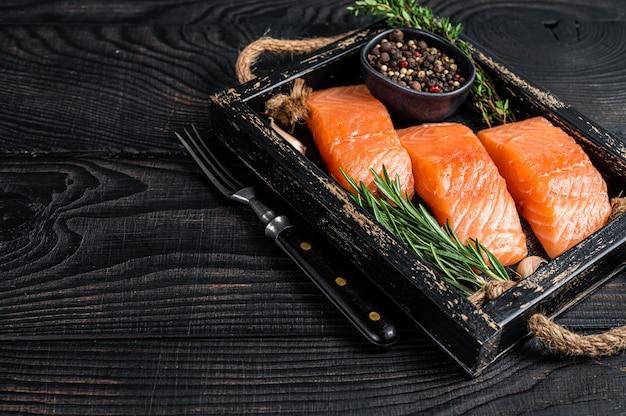 Стейки из сырого филе лосося на деревянном подносе с тимьяном и розмарином
