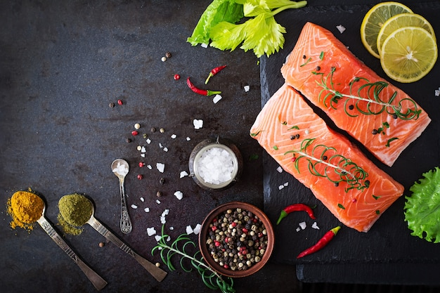 Raw salmon fillet and ingredients for cooking on a dark surface in a rustic style.