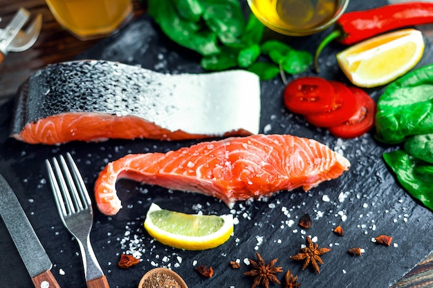 Raw salmon fillet and ingredients for cooking on a dark wall.