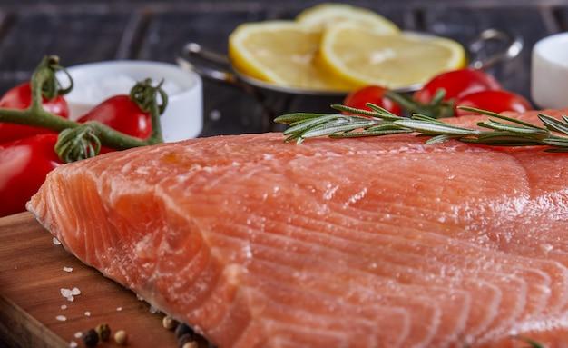 Сырые филе лосося перец соль укроп лимон розмарин и помидоры черри на темный деревянный стол.