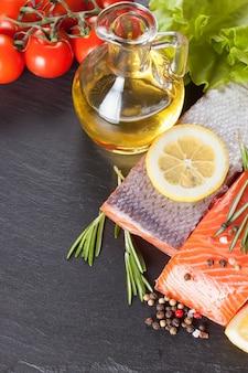 Сырое филе лосося, специи и овощи на темном сланцевом столе
