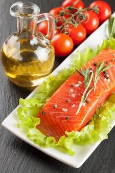 Сырое филе лосося, специи и овощи на белой тарелке