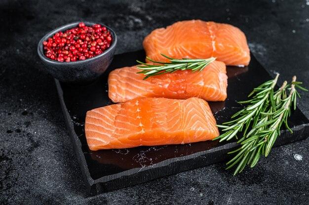 Стейки из сырого филе лосося на мраморной доске с зеленью