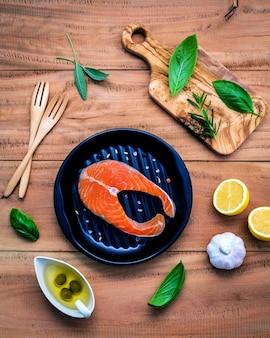 Raw salmon fillet with ingredients  on wooden background .