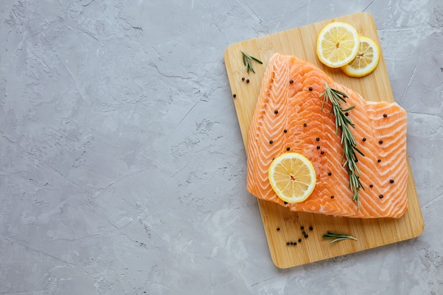 Raw salmon fillet with lemon rosemary and pepper on cutting board fresh organic wild atlantic fish on grey stone background top view mediterranean cuisine healthy and diet food concept
