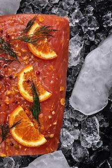 Сырое филе лосося с дольками апельсина на кусочках льда на черном фоне