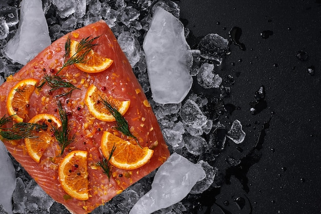 Raw salmon fillet with orange slices on pieces of ice on a black background