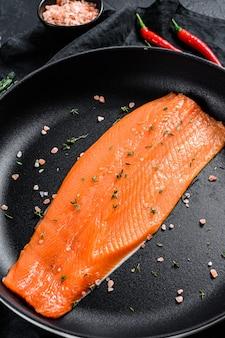 Сырое филе лосося с солью и перцем чили на сковороде