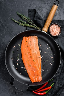 Raw salmon fillet with salt and chili pepper in a pan. organic fish
