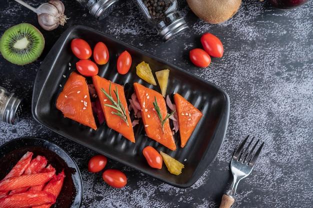 生の鮭の切り身、コショウ、キウイ、パイナップル、ローズマリーをプレートと黒いセメントの床に。