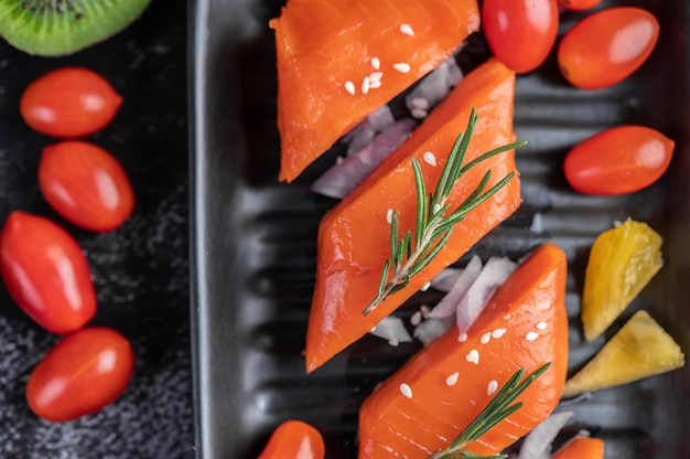 Raw salmon fillets, pepper, kiwi, pineapples, and rosemary onto a plate and black cement floor.