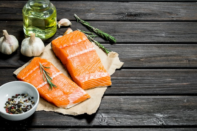 Raw salmon fish filet with garlic and herbs. on a wooden background.