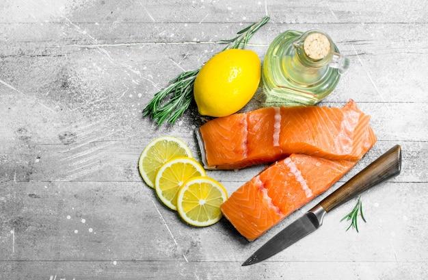 Сырое филе лосося с лимоном и розмарином. на деревенском фоне.