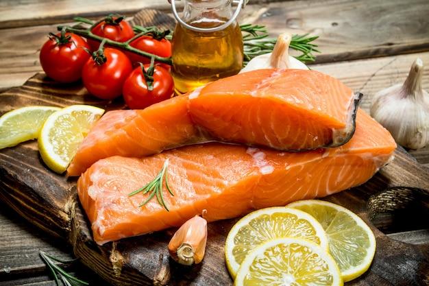 Сырое филе лосося с лимоном, помидорами и зеленью. на деревянном.