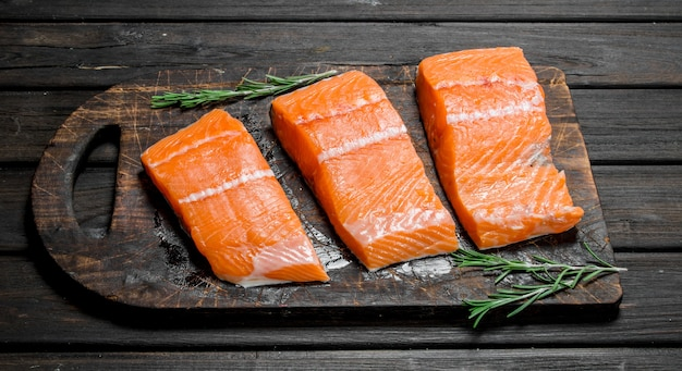 Raw salmon fish filet with rosemary. on a wooden.