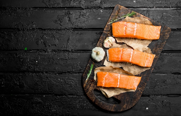 Raw salmon fish filet with spices. on black rustic background.
