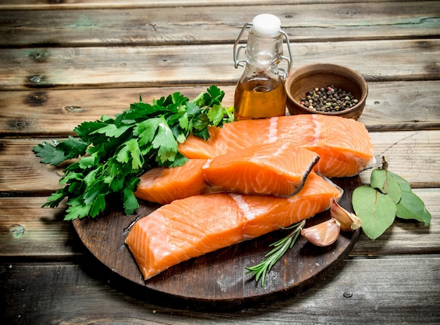 Raw salmon fish filet with spices and fresh parsley on rustic table.