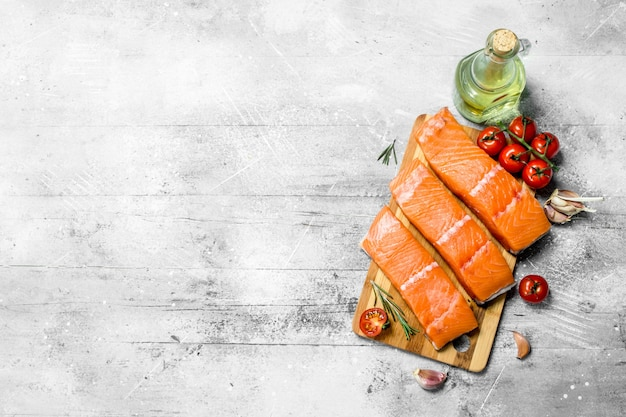 Raw salmon fish filet with spices, herbs and ripe tomatoes on a rustic table.