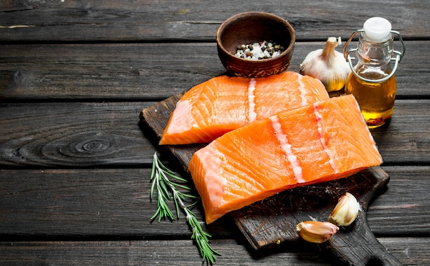Raw salmon fish filet with spices and herbs. on a wooden background.