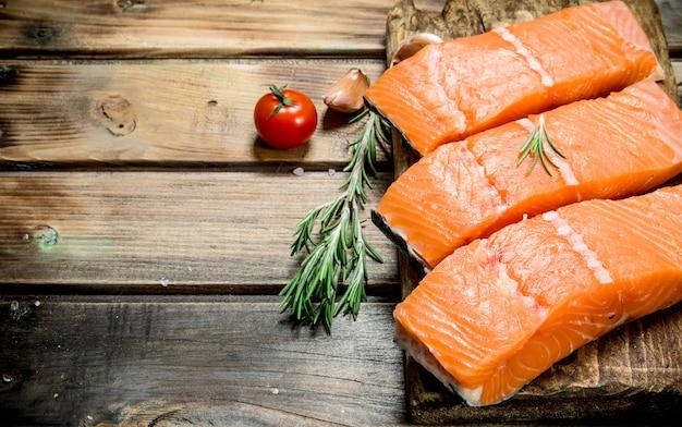Сырое филе лосося с помидорами и специями. на деревянном фоне.