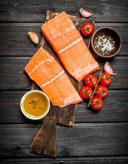 Сырое филе лососевой рыбы с помидорами и специями на деревянном столе.