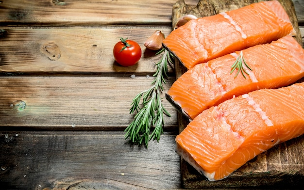 Raw salmon fish filet with tomatoes and spices. on a wooden background.