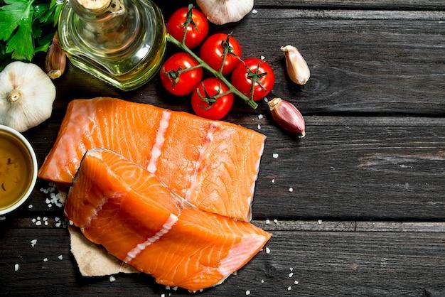 Сырое филе лосося с овощами, специями и оливковым маслом на деревянном столе.