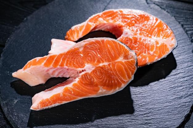 Raw salmon fish fillet on black surface