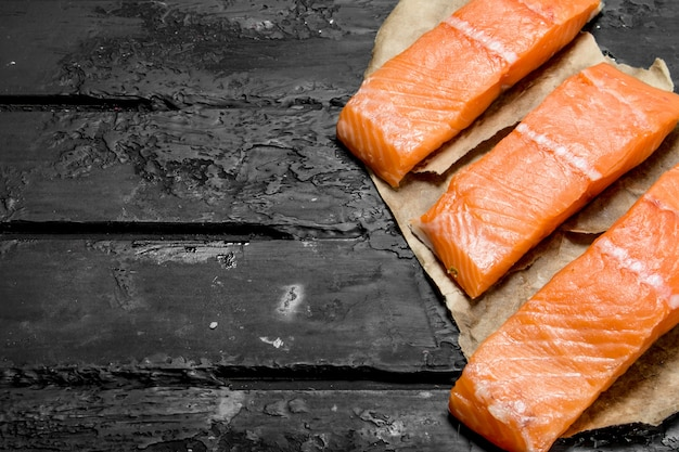 Raw salmon fish steaks on paper on rustic table.