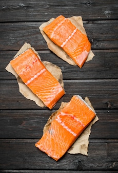 Raw salmon fish steaks on paper on wooden table.