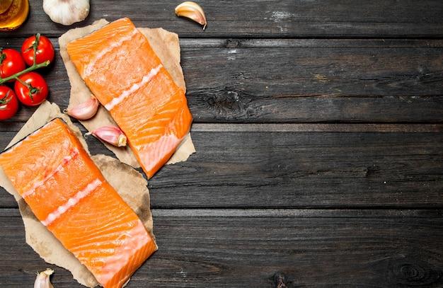 Стейки из сырой рыбы из лосося с чесноком и помидорами. на деревянном фоне.