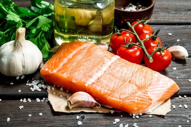 Стейки из сырой рыбы из лосося с чесноком и помидорами. на деревянной поверхности.