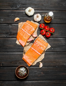 Raw salmon fish steaks with garlic and tomatoes on wooden table.
