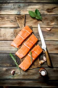 Стейки из сырой рыбы из лосося с зеленью и чесноком. на деревянном столе