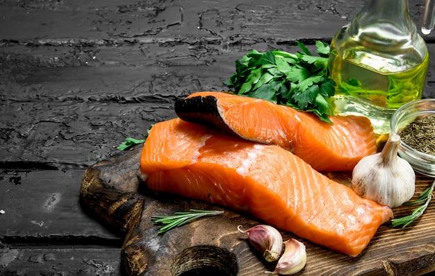 Стейки из сырой рыбы из лосося с травами и специями. на черном деревенском.