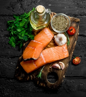 Raw salmon fish steaks with herbs and spices on black rustic table.
