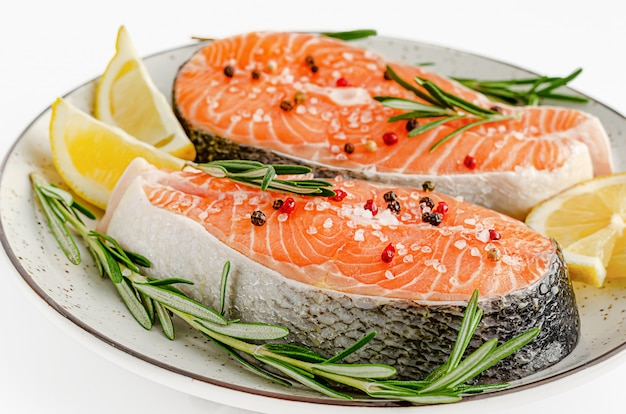 Raw salmon fish steaks with pepper, sea salt, rosemary and lemon on white. top view, keto diet and healthy eating concept.