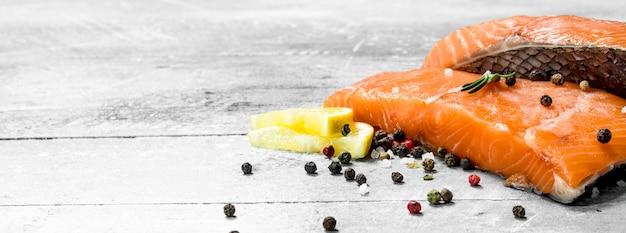 Стейки из сырой рыбы из лосося со специями и дольками лимона. на деревенском столе