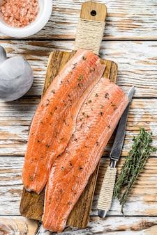 Сырое филе морской рыбы из лосося или форели со специями и зеленью.