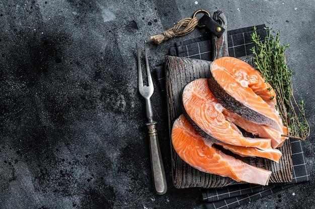 Сырые стейки из лосося или форели, рыба, приготовленная для приготовления на деревянной доске. черный фон. вид сверху. скопируйте пространство.