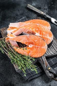 Сырые стейки из лосося или форели, рыба, приготовленная для приготовления на деревянной доске. черный фон. вид сверху.