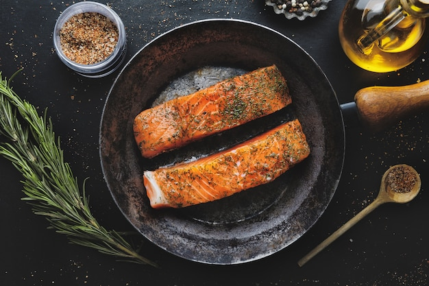 Raw salmon pieces with spices and dill on pan