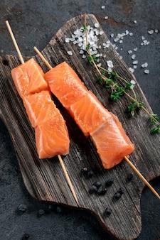 나무 판자에 아시아 스타일로 굽기 위한 생 연어 꼬치. 해산물 바베큐 레시피