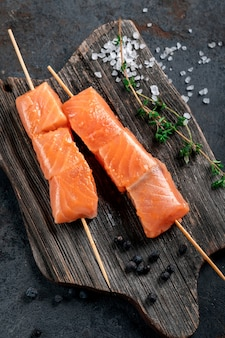 Raw salmon skewers for grilling in the asian style on wooden board. seafood barbecue recipe