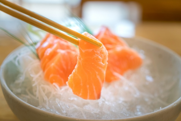 Raw salmon slice or salmon sashimi in japanese style fresh serve on ice in bowl.