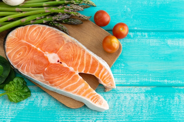Raw salmon slice with vegetable decoration on blue surface. copy space. Premium Photo