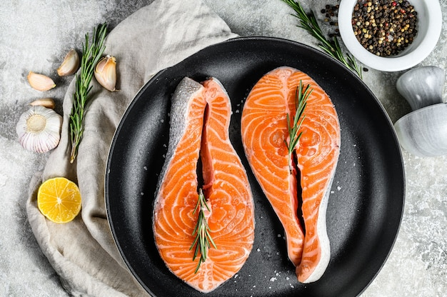 Raw salmon steak in a frying pan. healthy seafood. gray background. top view