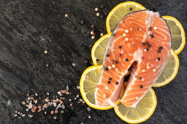 レモンスライスに生のサーモンステーキ、黒い石にソルトとペッパー、上面図 Premium写真