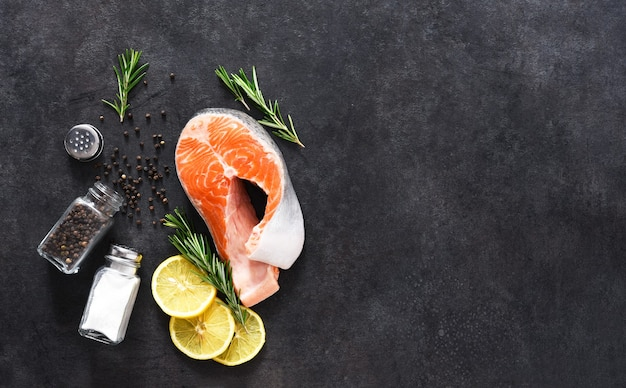 Сырой стейк из лосося, соль и розмарин на конкретном черном фоне. ингредиенты для приготовления рыбы.