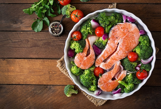 Raw salmon steak and vegetables for cooking on a dark wooden background in a rustic style. top view